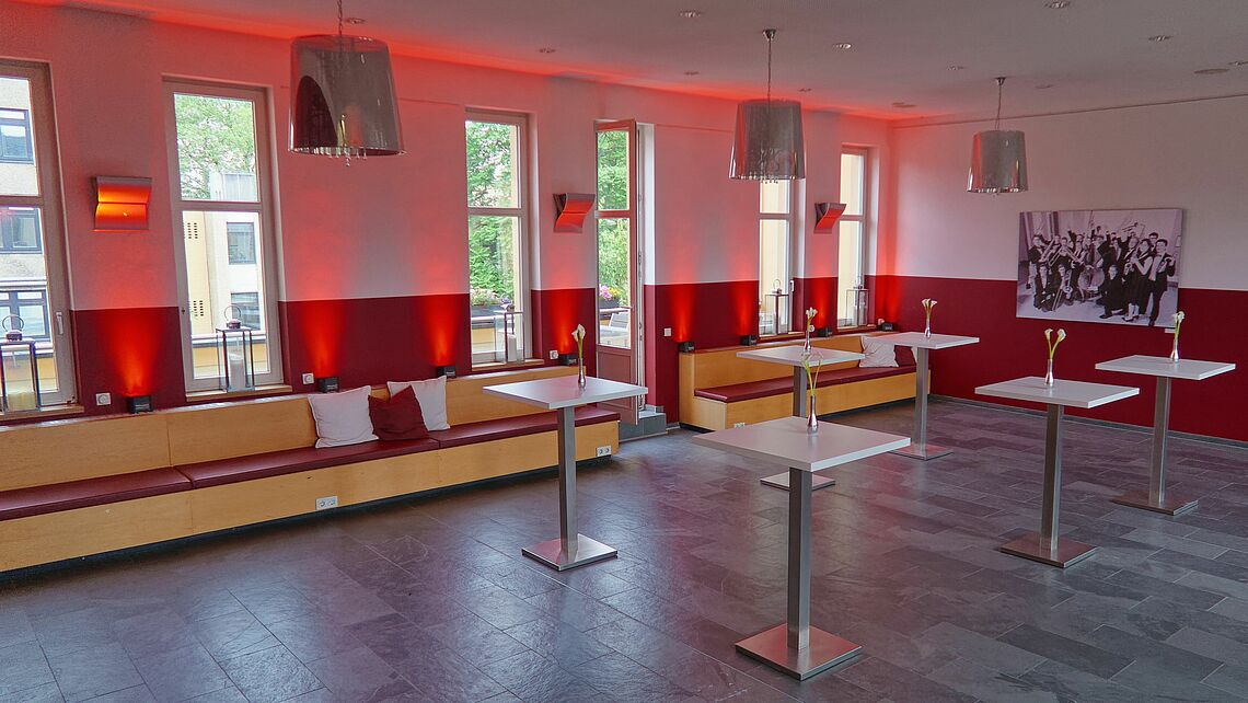 An angled view of the South Lounge from one corner of the space: bar tables and the integrated bench span the length of the room while access to one of the balconies is visible in the background; red LED spots have been used to illuminate the walls