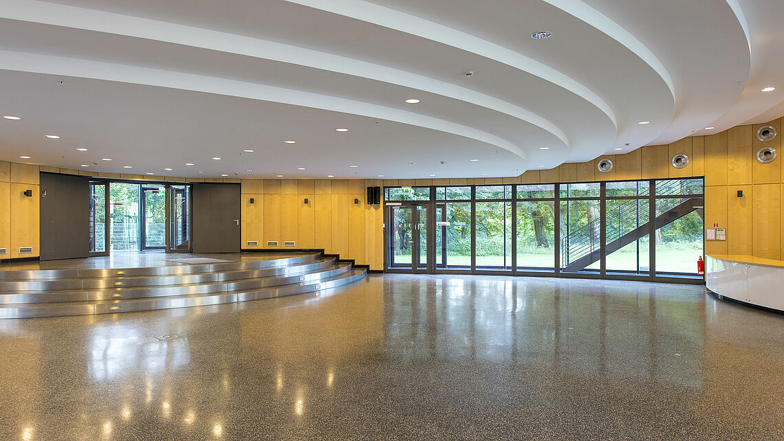 Ground Level: A view of the foyer and highly customizable reception space; a sink and service counter are located on the far right edge of the image while steps leading to the upper level are visible in the background (not pictured: the elevator)